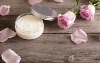 cosmetic cream with pink roses on old wooden table