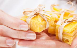 Woman hands holding pieces of natural beeswax, packed and decorated