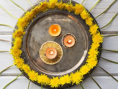 Pattern with dandelions and candles on a metal tray