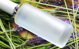 a bottle with fresh cologne and a pile of lavender flowers