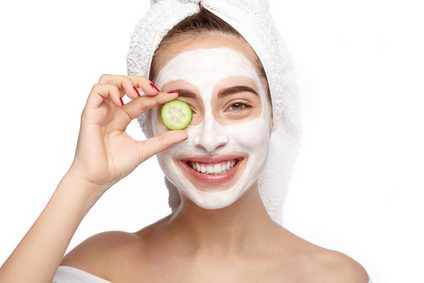 Cheerful woman closing eye with cucumber during the spa procedures.